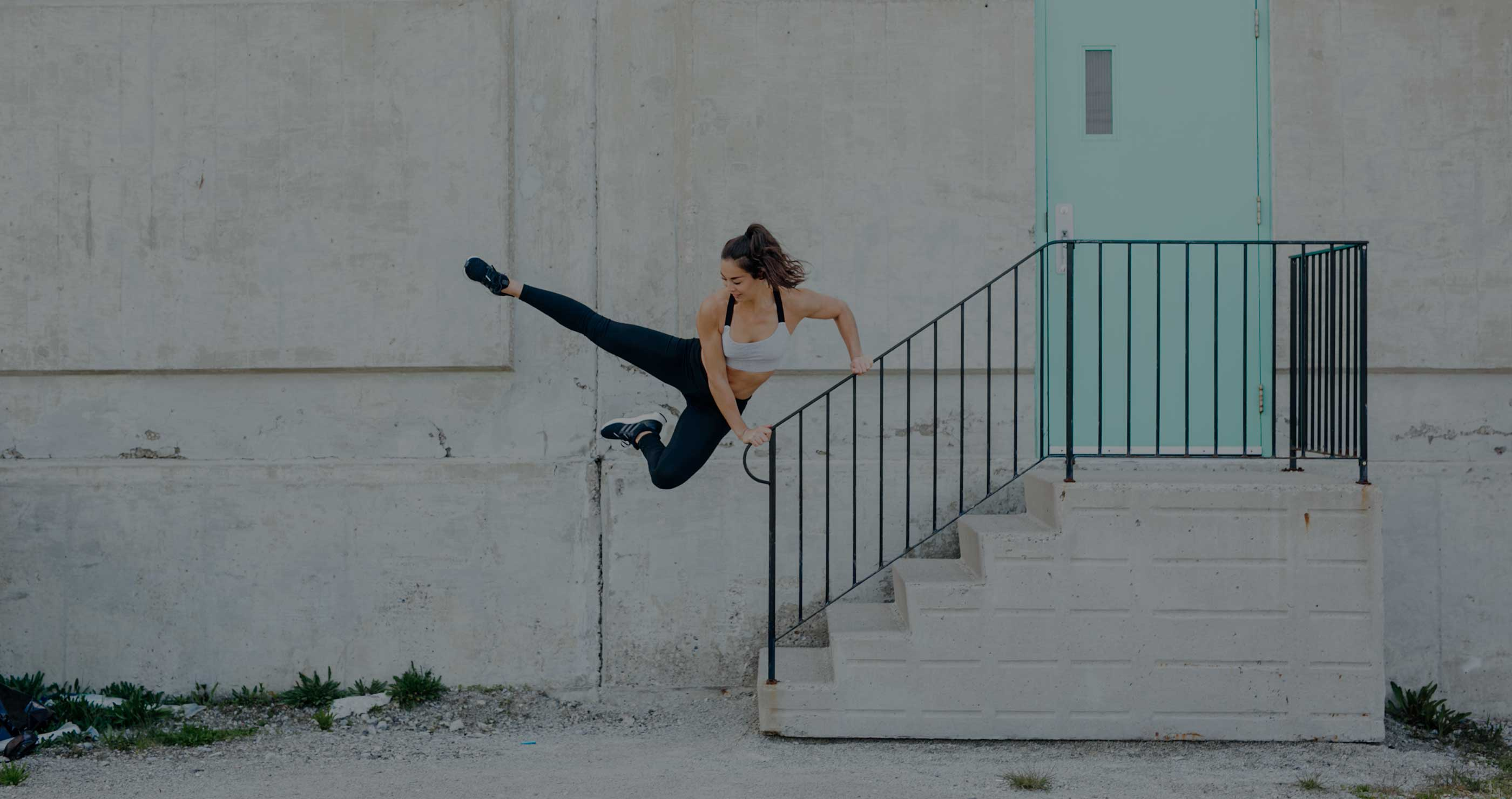 Beverly Cheng from Born to Sweat holding on to a railing while lifting both feet up in the air